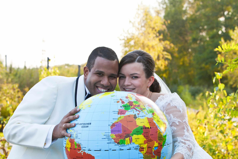 Das Brautpaar hält einen Globus in der Hand und schaut lachend darüber hinweg. Im Hintergrund sind goldgelbe Blätter und Bäume.