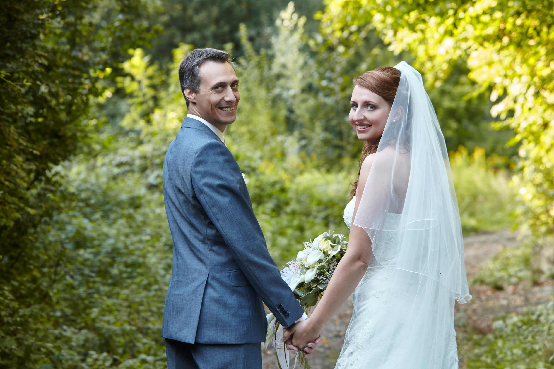 Das Brautpaar steht Hand in Hand nebeneinander auf einem Waldweg. Beide lachen. Die Braut hält einen Brautstrauß in der Hand.