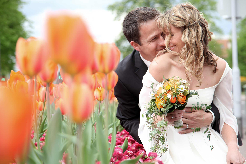 Das Brautpaar lächelt sich verträumt an. Der Bräutigam hält die Braut im Arm. Die Braut hält einen Brautstrauß in der Hand. Im Vordergrund sind orangefarbene Blumen.