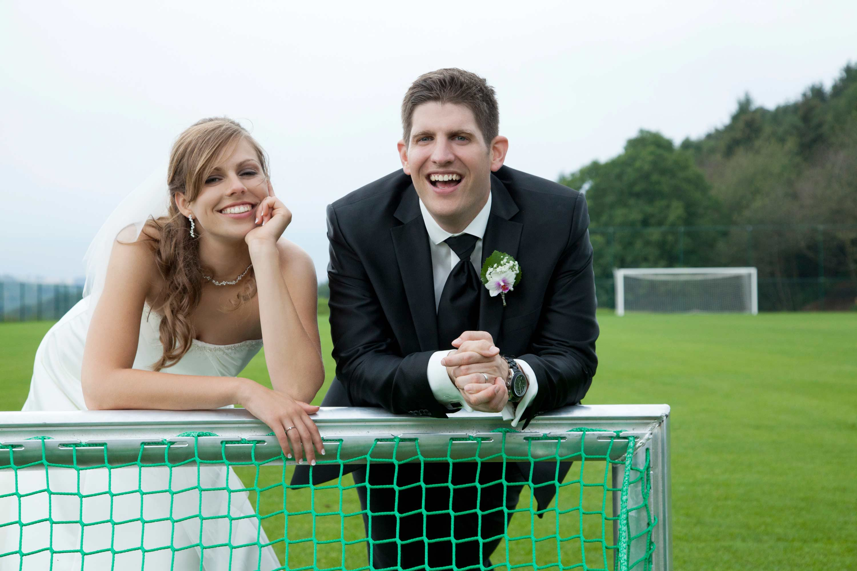 Das Brautpaar stützt sich lässig auf eine Fussballtor. Beide lachen. Im Hintergrund sieht man einen Fussballplatz.