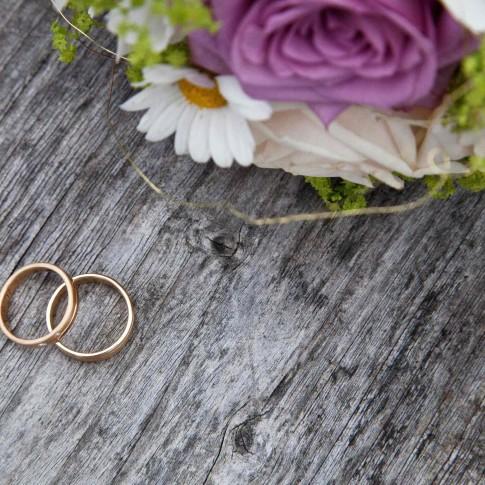 Goldene Trauringe drapiert auf Holz. Daneben liegt der Brautstrauß der nur angeschnitten zu sehen ist.
