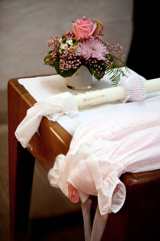Auf einem Holztisch drapiert sind ein buntes Gesteck, Taufkerze und ein weißes Taufkleid.