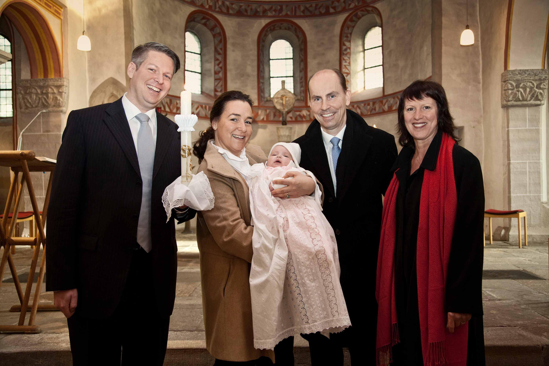 Taufshooting mit Taufkind, Taufeltern und Paten. Die Eltern tragen das Kind mittig von sich. Außen stehen rechts und links die Taufpaten. Das Taufkind trägt ein traditionelles weißes Taufkleid.
