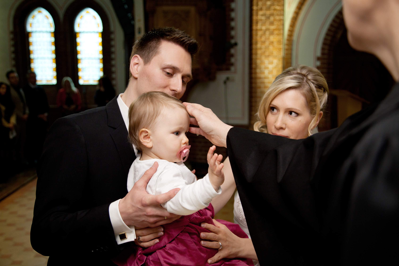 Der Priester erteilt dem Kind den Taufsegen. Er berührt das Taufkind am Kopf. Das Kind wird vom Vater und der Mutter gehalten.