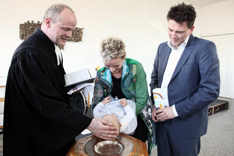 Das Taufkind bekommt vom Priester über dem Taufbecken den Taufsegen. Die Mutter hält das Kind über das Taufbecken. Der Vater steht im blauen Anzug neben seiner Frau und hält die Taufkerze in der Hand.
