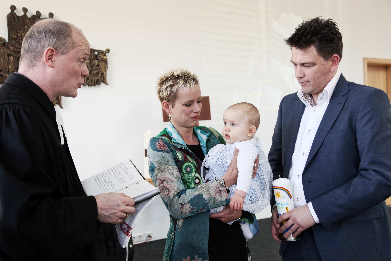 Der Priester liest etwas vor. Die Mutter trägt das Taufkind auf dem Arm. Das Taufkind trägt ein Taufkleid. Der Vater steht mit der Taufkerze neben seiner Frau und dem Taufkind.