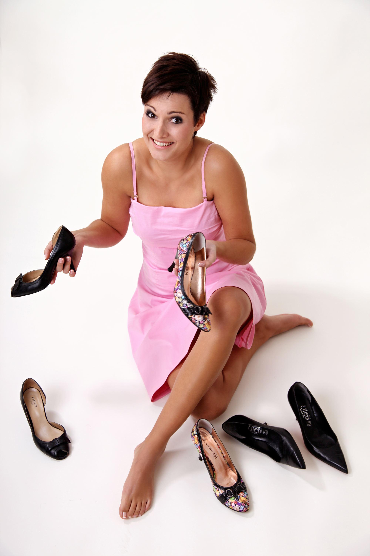 Die Verlobte ist in einem rosa Kleid abgebildet. Sie sitzt auf weißem Untergrund auf dem Boden und vor ihr liegen drei Paar Schuhe. Sie guckt fragend in die Kamera.