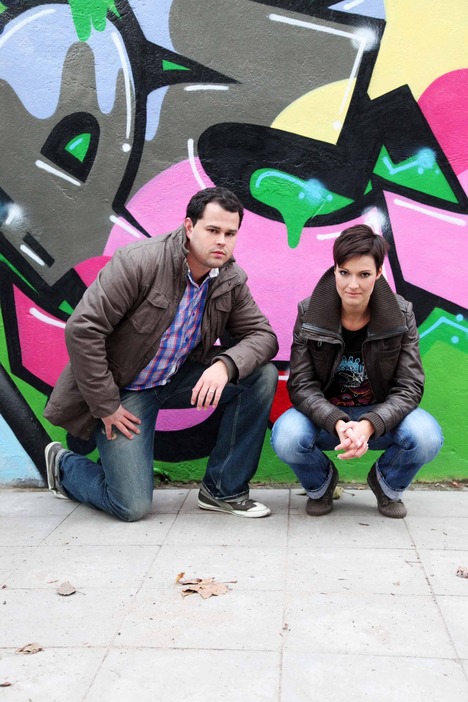 Verlobter und Verlobte vor einer Graffiti Wand. Sie ist in Jeanshose und Lederjacke gehüllt. Sie hockt vor der Wand. Der Mann kniet in der typischen Heiratsantragspose vor der Kamera.