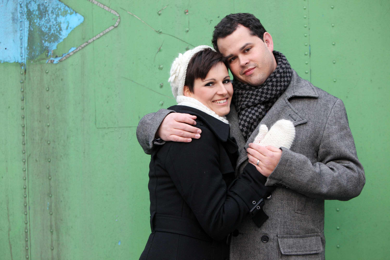 Das Verlobungspaar hält sich vor einem grünen Metallhintergrund in den Armen. Beide haben Winterkleidung an.