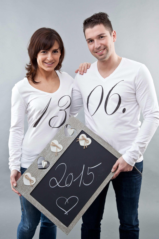 """Die Frau trägt ein weißes Shirt mit der Aufschrift """"13."""" und der Mann, ebenfalls im weißen Shirt, die Aufschrift """"06.""""! Vor sich halten sie eine Tafel wo das Jahr 2015 draufsteht. Zusammen ergibt es das Hochzeitsdatum."""