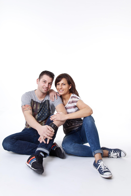 Das Verlobungspaar sitzt auf dem Boden im Shootingstudio. Beide sind lässig gekleidet. Sie legt ihre Hände auf seine Schulter und seinen Arm ab.