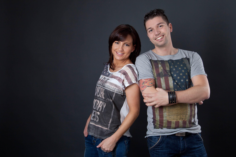 Verlobter und Verlobte tragen beide ein T-Shirt auf der die amerikanische Flagge zu sehen ist. Sie lehnen sich lässig seitlich aneinander. Beide gucken lächelnd in die Kamera.