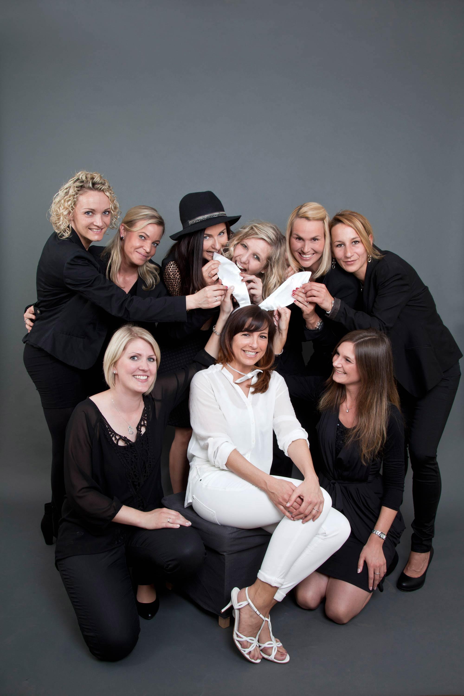 Junggesellinnenabschied. Die zukünftige Braut sitzt als einzige in weiß, mit Hasenohren, gekleidet in einer Schar Frauen, die allesamt in schwarz gekleidet sind.