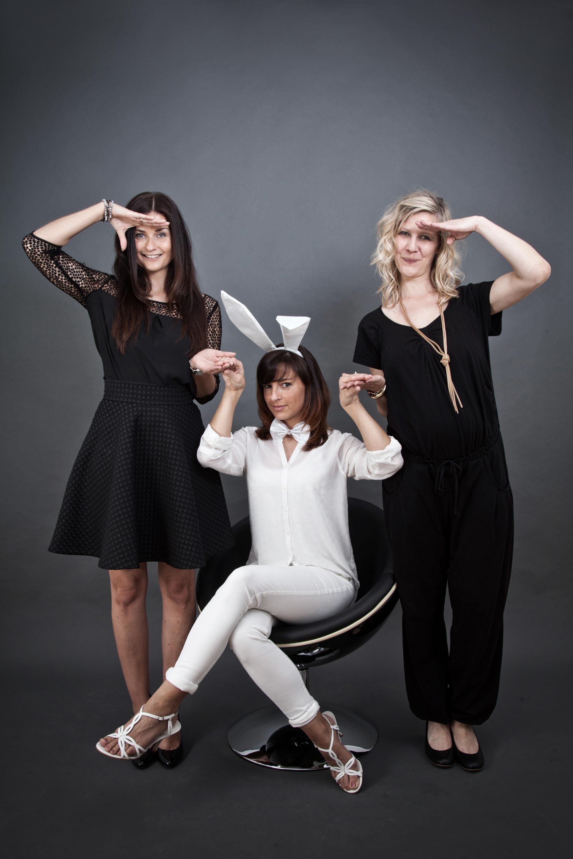 Eine Frau in weiß gekleidet sitzt auf einem schwarzen Stuhl. Rechts und links neben ihr stehen zwei Frauen. Die Frauen sind in schwarz gekleidet und halten mit der einen Hand die Frau in weiß an der Hand und mit der anderen salutieren sie.