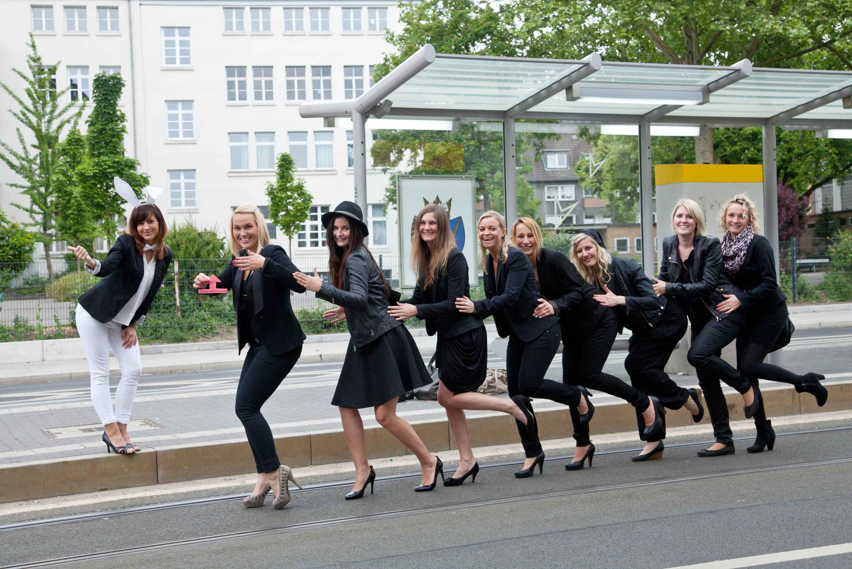 Shooting an einer Strassenbahnhaltestelle. Acht Frauen bilden hintereinander weg eine Karawane. Die zukünftige Braut steht an der Haltestelle und hält den Daumen nach oben.