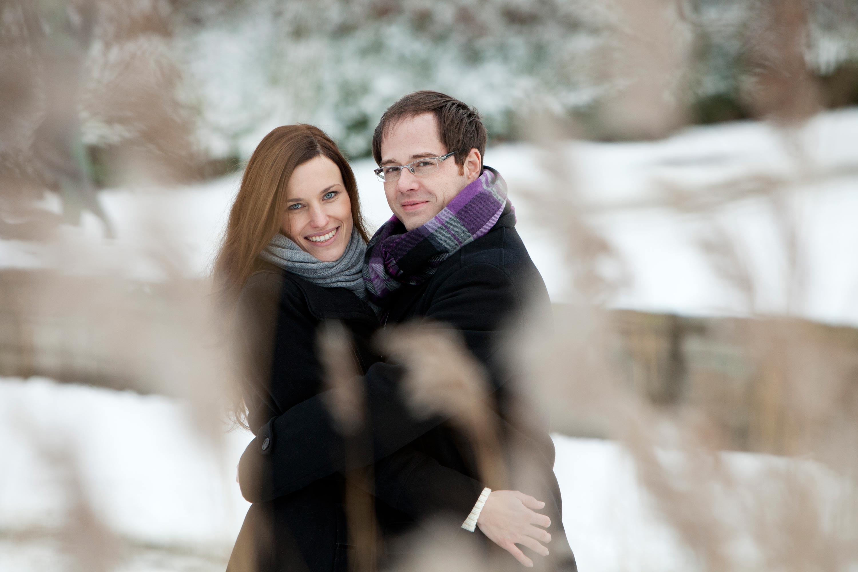 Verlobungspaar in inniger Umarmung im Winter. Schnee im Hintergrund. Beide tragen einen dunklen Wintermantel und einen Schal. Sie gucken seitlich lächelnd in die Kamera.