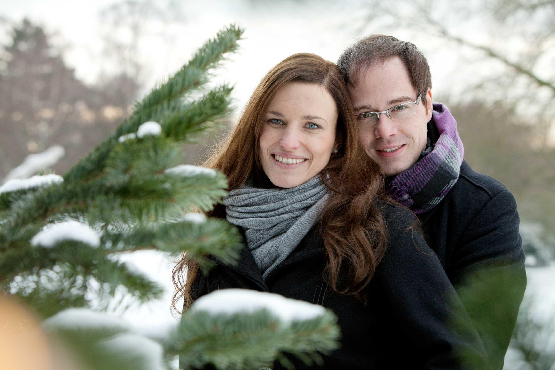 Verlobungspaar steht draußen im Schnee. Verlobter steht hinter seiner zukünftigen Frau und umarmt sie. Sie lächeln beide in die Kamera. Im Vordergrund ist ein Tannenzweig mit Schnee bedeckt.