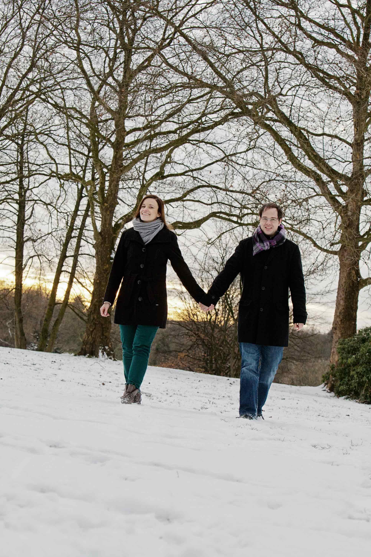 Händchenhaltend läuft ein Verlobungspaar durch den Schnee. Im Hintergrund stehen zwei große kahle Bäume.