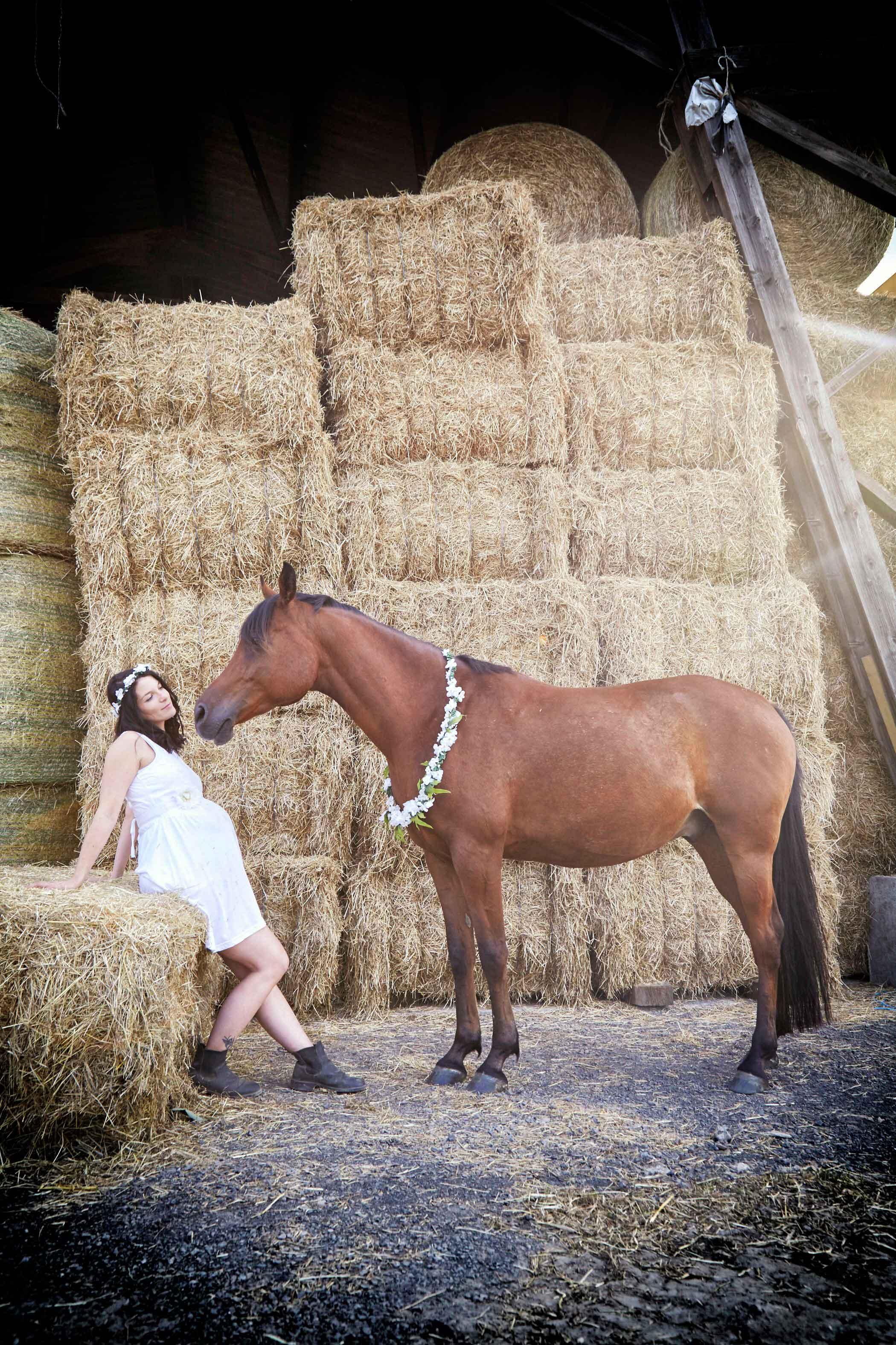 Schwangere Frau mit Babybauch sitzt im Stroh und schaut ihr Pferd an.